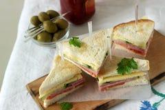 Sanduíches com salsicha, carne, queijo e os legumes frescos em uma tabela com azeitonas e ketchup foto de stock