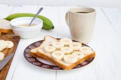 Sanduíches da banana na placa com copo de café Fotos de Stock