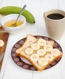 Sanduíches da banana na placa com copo de café Fotos de Stock Royalty Free