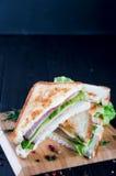 Sanduíches de clube no fundo de madeira Imagens de Stock