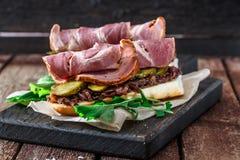 Sanduíches de Delicius com carne de porco fumado, pepinos e cebola em uma placa de madeira preta Foto de Stock