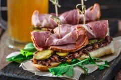 Sanduíches de Delicius com carne de porco fumado, pepinos e cebola em uma placa de madeira preta Fotografia de Stock