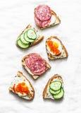 Sanduíches do aperitivo com caviar, o ovo, a salsicha, o pepino e queijo creme vermelhos no fundo branco imagens de stock