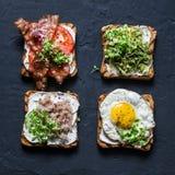 Sanduíches do café da manhã - o puré do abacate, ovo frito, tomates, bacon, queijo creme, cavala fumado grelhou o sanduíche intei fotos de stock