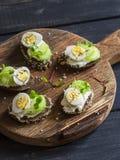 Sanduíches do queijo com ovos e aipo de codorniz em uma placa de corte rústica Foto de Stock Royalty Free