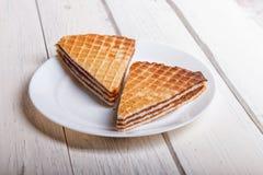 Sanduíches do waffle com leite condensado fervido na placa na tabela de madeira branca imagens de stock