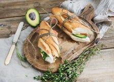 Sanduíches dos salmões, do abacate e do tomilho no baguette amarrado acima com corda da decoração em uma placa de madeira rústica Imagem de Stock Royalty Free
