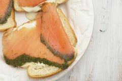 Sanduíches dos salmões, do queijo e do aneto na placa branca com fundo de madeira branco Imagem de Stock