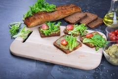 Sanduíches em uma mesa do corte Pão crocante do corte, folhas da salada, tomates vermelhos, óleos e molho do guacamole em uma tab imagens de stock royalty free