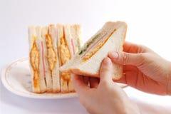 Sanduíches na mão da mulher Foto de Stock Royalty Free