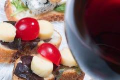 Sanduíches na placa e no vidro do vinho vermelho Fotos de Stock Royalty Free