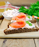 Sanduíches no pão com salmões a bordo Foto de Stock
