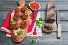 Sanduíches pequenos do canape com o caviar do vermelho dos peixes Fotos de Stock Royalty Free
