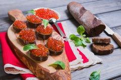 Sanduíches pequenos do canape com o caviar do vermelho dos peixes Foto de Stock