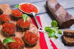 Sanduíches pequenos do canape com o caviar do vermelho dos peixes Imagens de Stock