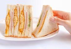 Sanduíches que estão sendo pegarados pela mão da mulher Foto de Stock Royalty Free