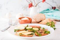 Sanduíches saborosos em uma placa e em forquilhas Fotografia de Stock Royalty Free