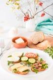 Sanduíches saborosos em uma placa e forquilhas em uma tabela Imagens de Stock