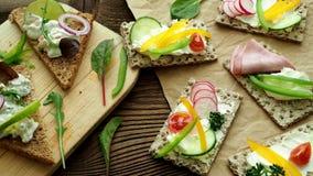 Sanduíches saudáveis com legumes frescos Brindes do café da manhã na placa de corte de madeira video estoque