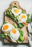 Sanduíches saudáveis do café da manhã na placa de madeira rústica sobre o fundo cinzento fotos de stock