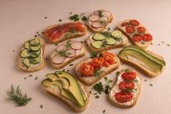 Sandu?ches com salm?es, pepino, tomates, abacates e verdes, vegetal cortado fotografia de stock