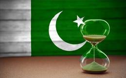 Sanduhr auf dem Hintergrund der Pakistan-Flagge, dem Konzept der Zeit und den Ländern, Raum für Text stockfoto