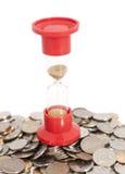 Sanduhr auf Münzen Stockfotos