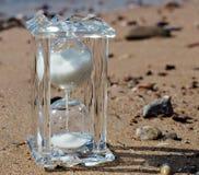 Sanduhr des Kristalles auf einem sandigen Strand Lizenzfreie Stockfotos