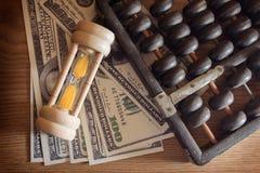 Sanduhr mit Abakus und Banknote Stockfoto