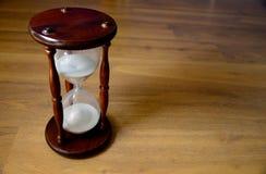 Sanduhr, Uhr vor hölzernem Hintergrund mit einem Kopienraum Lizenzfreie Stockfotografie