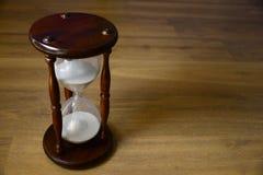 Sanduhr, Uhr vor hölzernem Hintergrund mit Kopienraum Zeit läuft weg Stockfotografie