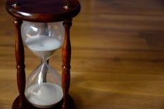 Sanduhr, Uhr vor hölzernem Hintergrund mit Textraum Zeit läuft weg Lizenzfreie Stockbilder