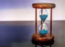 Sanduhrnahaufnahme nachdenkend und über Glastisch mit buntem blauem Hintergrund widergespiegelt Stockbild