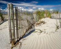 Sandune with Fence and Clouds Stock Images