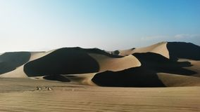 Sandunes in Ica, Peru. Sand dunes with shadows on a cloudless hot day royalty free stock photography