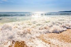 Sandwüstestrand und blauer Himmel nach Sonnenaufgang und Spritzen des Meerwassers Stockfoto