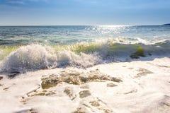 Sandwüstestrand und blauer Himmel nach Sonnenaufgang und Spritzen des Meerwassers Stockfotos