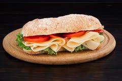 Sandwich à ciabatta avec de la laitue, le prosciutto et le fromage sur le conseil en bois photos libres de droits