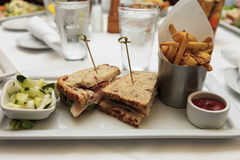 Sandwich à club de la Turquie et pommes frites avec des amis Photographie stock libre de droits