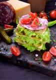 Sandwich à club posé multi avec du pain de seigle, la salade de laitue, la saucisse, le fromage, les concombres salés et les toma photo libre de droits