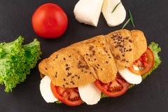 Sandwich à croissant avec du mozzarella et la tomate de laitue au-dessus du fond en pierre noir Casse-croûte sain Vue supérieure photo stock