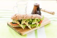 Sandwich à forme physique avec l'avocat et le fromage et le café noir Images libres de droits