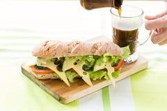 Sandwich à forme physique avec l'avocat et le fromage et le café noir Image libre de droits