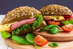 Sandwich à hamburger avec du jambon, le fromage, les tomates et la laitue Images libres de droits