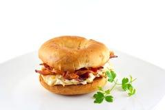 Sandwich à lard et à oeufs sur un bagel d'oignon Photographie stock