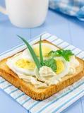 Sandwich à petit déjeuner avec les oeufs et le feuillage coupés en tranches photographie stock libre de droits