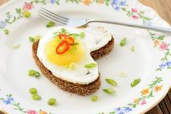 Sandwich à seigle de coeur d'oeuf au plat avec l'oignon blanc, le piment et la fourchette sur le wh Photos libres de droits