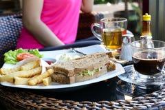 Sandwich à thon de plat et pommes chips, café, thé avec la femme sur Photos libres de droits