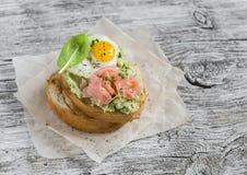 Sandwich écrasé à avocat avec les saumons fumés et l'oeuf sur le plat de caille Un petit déjeuner ou un casse-croûte délicieux Images stock