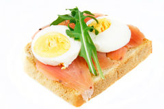 Sandwich. Delicious sandwich with salmon, hard-boiled egg and rucola. Nutritious breakfast Royalty Free Stock Images